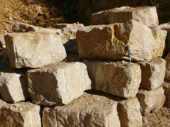 Gezeigt werden hier mehrere aufeinandergeschichtete, teils rechteckige, teils quadratische rötlich graue Steinblöcke. Ein angelehnter Hammer auf einem der rechtwinkligen Blöcke rechts dient als Größenvergleich.