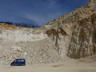Blick auf die meist rötlich graue Abbruchwand in einem Steinbruch. Rechts steigt die Wand steil an, links liegt vor hellerem Gestein ein großer Schuttberg. Ein kleiner blauer Kastenwagen steht davor.