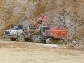 Das Bild zeigt einen orangenen Bagger und ein Transportfahrzeug vor einer Abbauwand in einem Steinbruch. Der Bagger lädt gerade Material auf das Fahrzeug.