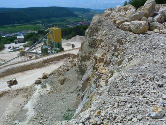 Blick von erhöhtem Standpunkt über einen Steinburch und dessen Förderanlage. Die rechte vordere Bildhälfte wird von einer Abbauwand eingenommen, im Hintergrund sind bewaldete Hügel zu sehen.