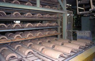 Das Bild zeigt zahlreiche halbrunde, rötlich braune Dachziegel, die in einem Metallregal gelagert sind.