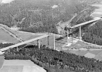 Das schwarzweiße Luftbild zeigt den Bau einer Brücke, über die eine mehrspurige Straße führen soll. Die Brücke überspannt ein Flusstal.