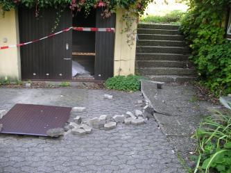Das Bild zeigt Schäden an einem Gebäudeteil links sowie aufgewölbte Wegplatten rechts und herausgebrochene Steine in der Mitte.