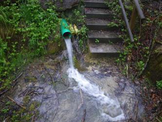 Das Bild zeigt drei offene Plastikrohre mit abfließendem Wasser am Fuß eines felsigen Hanges. Rechts davon verläuft eine Steintreppe mit Geländer.
