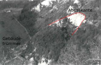 Luftbild, das rechts die Abrisskante einer Hangrutschung zeigt. Links unten sind Gebäudetrümmer erkennbar.