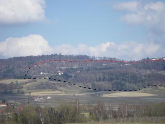Im Hintergrund befindet sich ein bewaldeter Bergrücken, in den mit gestrichelten Linien die Ausmaße der Rutschung eingezeichnet sind. Im Vordergrund Felder, vereinzelt Häuser