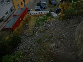 Blick von oben auf einen Geröllhang und dahinter einen abgesperrten Hof. Im Hintergrund sind Gebäude und Fahrzeuge zu sehen.