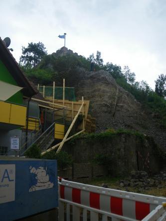 Das Bild zeigt ein Steinschlagereignis: Im Hintergrund des Bildes ist der Hang zu sehen, im Vordergrund links befindet sich ein abgesicherten Haus.