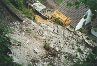 Aufsicht auf einen Felssturz, der sich von links unten gelöst hat. Rechts oben steht ein Wohnhaus.