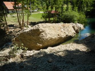Das Bild zeigt einen sehr großen Felsblock, der in einem Bachbett liegt. Der Bach hat sich davor aufgestaut. Das Ufer des Baches wird von Bäumen gesäumt. Im Hintergrund ist eine Wiese, eine Straße sowie ein Gebäude zu sehen.