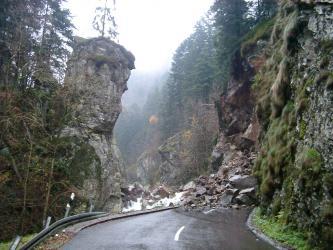 Zu sehen ist eine Straße, die von grobkörnigem Lockermaterial mehrere Meter hoch zugeschüttet ist. Die Straße wird an beiden Seiten von steilen, teils überhängenden Felsnasen begrenzt.