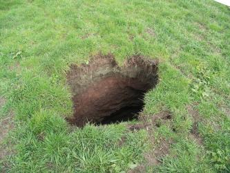 Der Blick richtet sich von oben auf eine grüne Rasenfläche, in deren Mitte ein Loch unbestimmter Tiefe im braunen Erdboden zu erkennen ist.