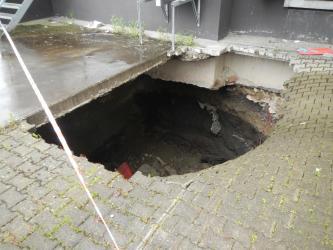 Zu sehen ist die Ecke einer Gebäudewand, davor ein Boden mit Pflastersteinen. In der Bildmitte ist der gepflasterte Untergrund eingestürzt. Ein großes Loch gibt den Blick auf das Gebäudefundament und das Erdreich unter den Pflastersteinen frei.