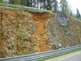 Zu sehen ist eine Straßenböschung, in deren Mitte sich eine trichterförmige Einsackung bemerkbar macht, die sich mit rötlich braunem Material auch farblich vom umgebenden Gestein absetzt.