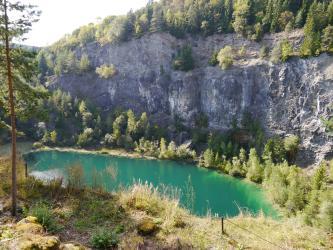 Von erhöhtem Standpunkt aus blickt man auf die hohe, unregelmäßig geformte und überwiegend graue Wand eines Steinbruches. Kuppe und Fuß des Steinbruches sind bewaldet; am Fuß liegt außerdem ein blaugrüner See.