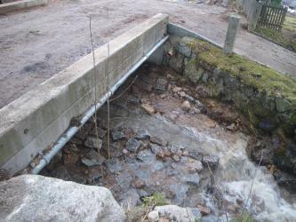 Zu sehen ist ein Teil einer steinernen Brücke, unter der ein Bach fließt. Darüber verläuft eine stark verschmutzte Straße.