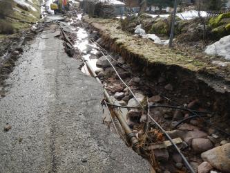 Auf dem Bild ist eine Straße, deren Asphalt auf der rechten Seite abgebrochen und so der Untergrund zu sehen ist. Zum Vorschein kommen einige Rohre und Kabel. Im Hintergrund ist ein Bagger zu sehen.