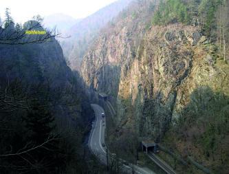 Der Blick richtet sich auf eine Straße, die durch eine Schlucht führt. Links und rechts der Straße ragen schroffe Felswände in die Höhe. Im Hintergrund sind bewaldete Berge zu erkennen.