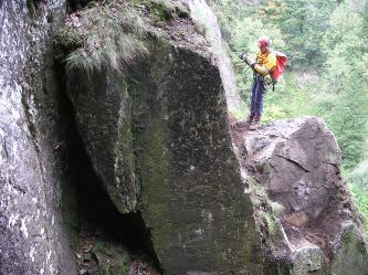 Zu sehen ist ein massiver Felsblock an einer Felswand. Auf einem Vorsprung steht ein gesicherter Kletterer und blickt nach unten.