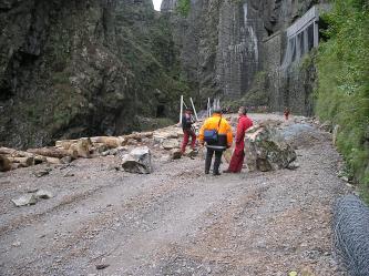 Auf dem Bild ist eine Straße zu sehen, die von hohen Felswänden gesäumt wird. Auf der Straße liegen mehrere größere Steinblöcke und Schotter. Vier Personen in Arbeitskleidung stehen in der Mitte des Bildes und begutachten das Ganze.