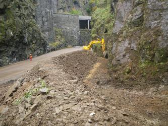 Das Bild zeigt eine Straße, die von zwei hohen Felswänden gesäumt ist. An der rechten Straßenseite steht ein Bagger, der einen Wall aus Steinen und Geröll aufhäuft. In der Straßenmitte steht eine Person in Warnweste und begutachtet die Szenerie.