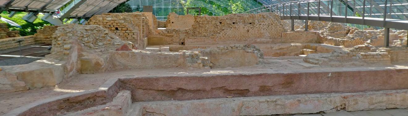 Blick auf die Reste eines römischen Bades. Im Vordergrund der Einstiegsbereich, dahinter Einfassungsmauern und rötliche Ziegelwände. Die Ruine ist überdacht.